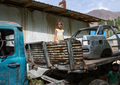 Tajik girl playing in old cars wrecks, Gorno-Badakhshan autonomous region, Khorog, Tajikistan