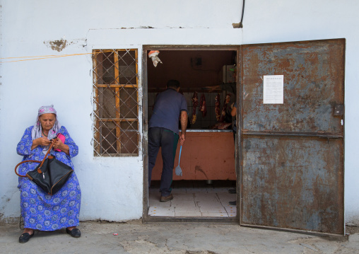 Tadik woman sit in front of the entrance of a butchery, Gorno-Badakhshan autonomous region, Khorog, Tajikistan