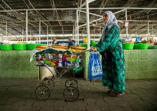 Old tajik woman selling some bread in a pram in a covered market, Gorno-Badakhshan autonomous region, Khorog, Tajikistan