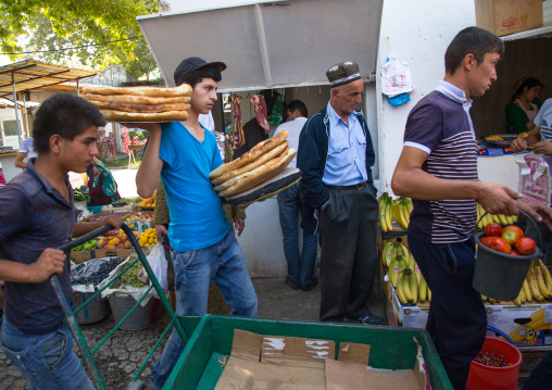 Young men carrying breads and fruits in the alleys of a local market, Gorno-Badakhshan autonomous region, Khorog, Tajikistan