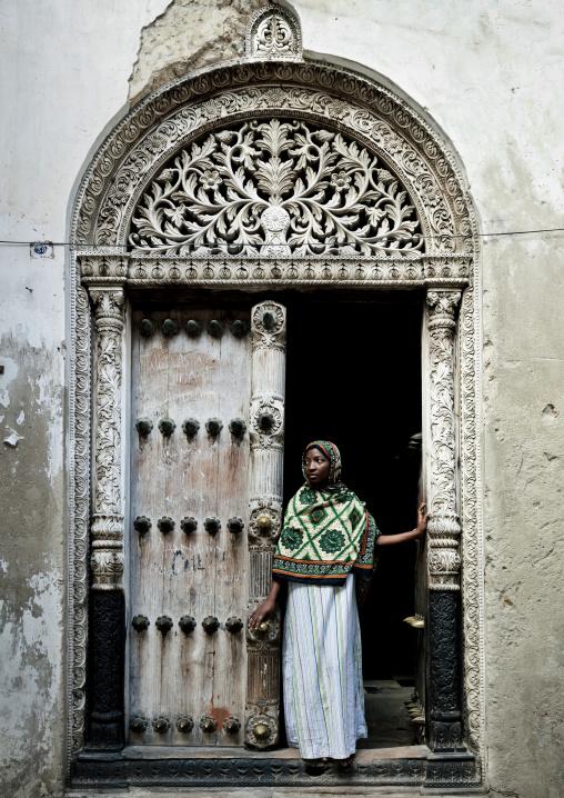 Swahili girl standing in front of  an old door in stone town zanzibar, Tanzania