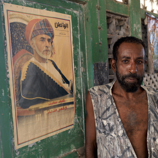 Witchdoctor in front of qaboos sultan portrait from oman, Stone town zanzibar, Tanzania