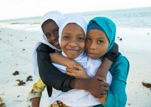Tanzania, Zanzibar, Kizimkazi, young muslim girls in school uniform running on beach