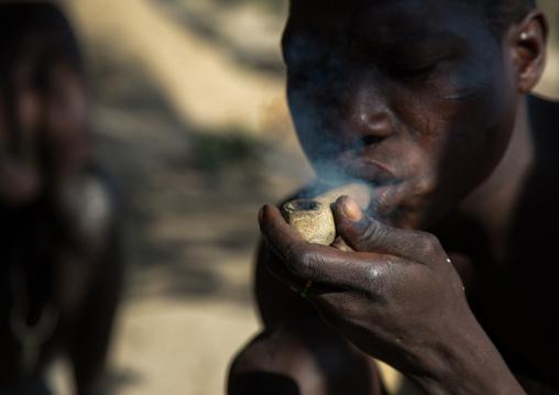 Tanzania, Serengeti Plateau, Lake Eyasi, hadzabe tribe man smoking cannabis