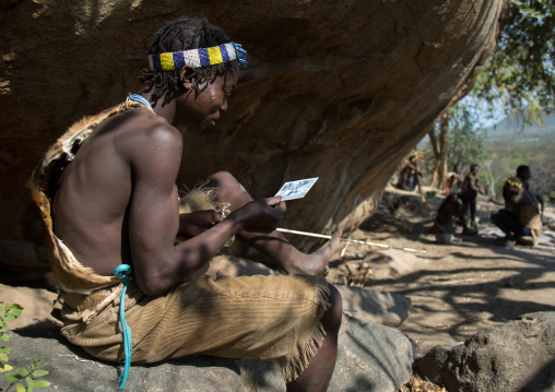 Tanzania, Serengeti Plateau, Lake Eyasi, hadzabe tribe man discovering his face on a polaroid