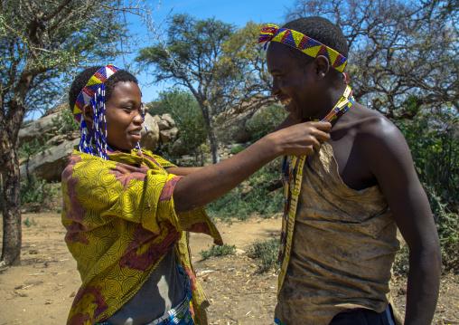 Tanzania, Serengeti Plateau, Lake Eyasi, hadzabe tribe woman offeringa necklace to a man to show him her love
