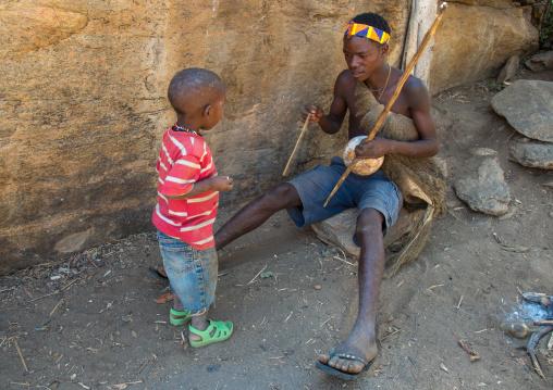 Tanzania, Serengeti Plateau, Lake Eyasi, hadzabe tribe man playing music to his child