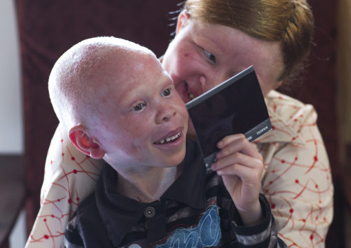 Tanzania, East Africa, Dar es Salaam, mariam staford and baraka cosmas people with albinism looking at a polaroid picture at under the same sun house