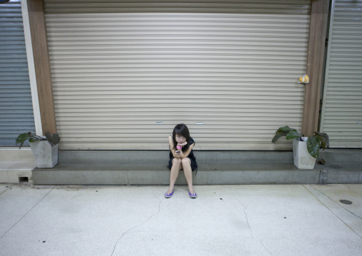 Girl looking at her mobile phone in the street, Bangkok, Thailand
