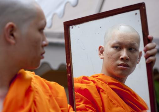 Novice looking at himself in a mirror, Bangkok thailand