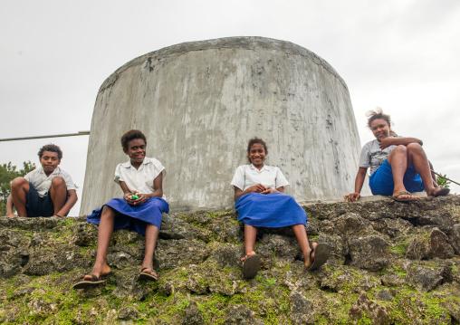 Teenagers in school uniforms sit in front of a concrete water tank, Shefa Province, Efate island, Vanuatu