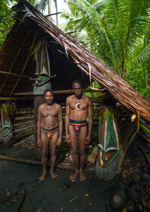 Portrait of chieftain Sekor and his father in front of a painted grade statue, Ambrym island, Olal, Vanuatu