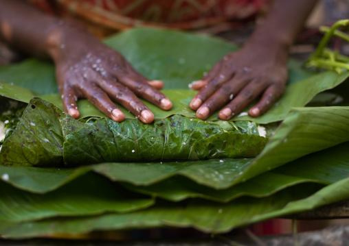 Woman cooking a bougna in a green banana leaf, Tanna island, Epai, Vanuatu