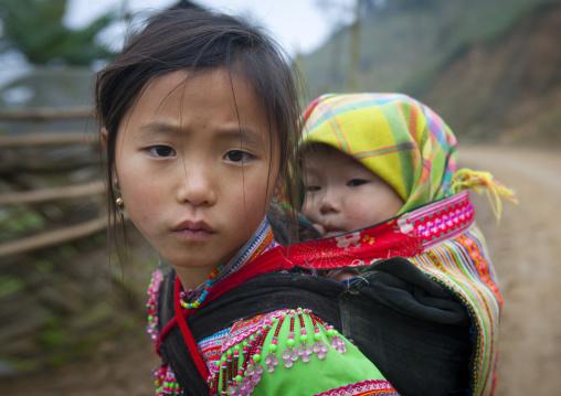Flower hmong girl carrying her baby sister on her back, Sapa, Vietnam