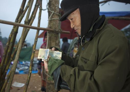 Old man showing the money he earned, Sapa, Vietnam