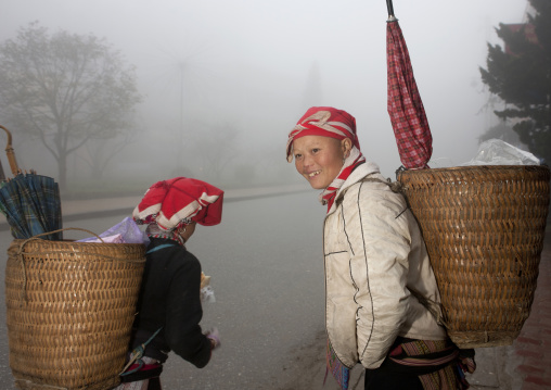 Red dzao women carrying umbrellas in the baskets on their back, Sapa, Vietnam