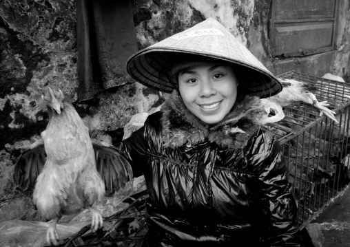 Woman with a sedge hat showing a chicken she sells, Sapa, Vietnam