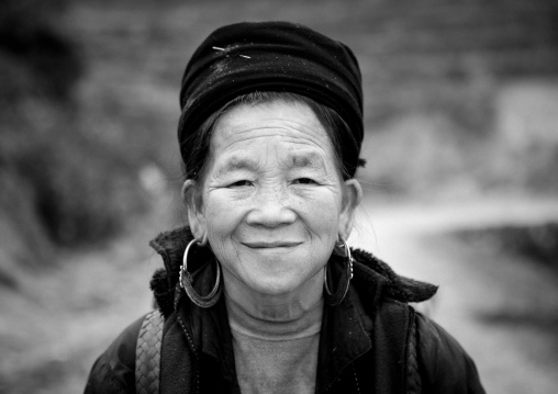Smiling old black hmong woman with traditional hat and earrings, Sapa, Vietnam