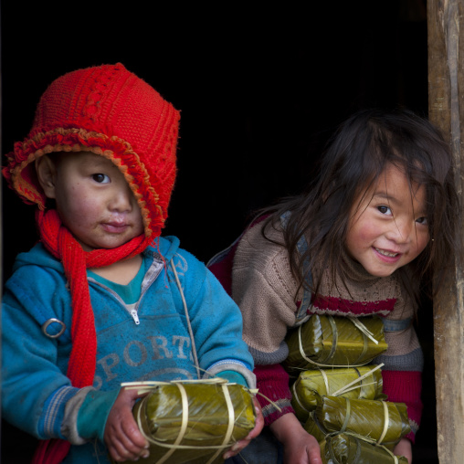 Black hmong kids holding wrapped rice cakes for tet, Sapa, Vietnam