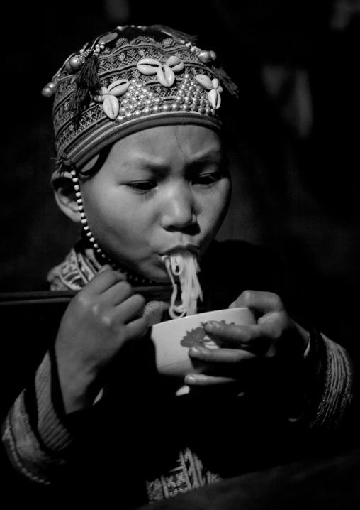 Red dzao girl eating noodles, Sapa, Vietnam
