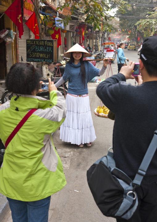 Couple of tourists taking a picture of a woman with a sedge hat, Hanoi, Vietnam