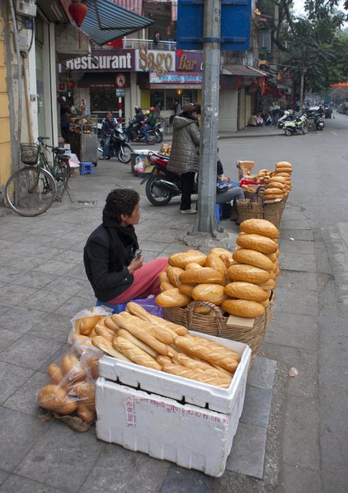 Woman selling bread in the street, Hanoi, Vietnam