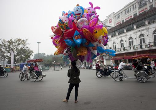 Woman selling balloons in the street, Hanoi, Vietnam