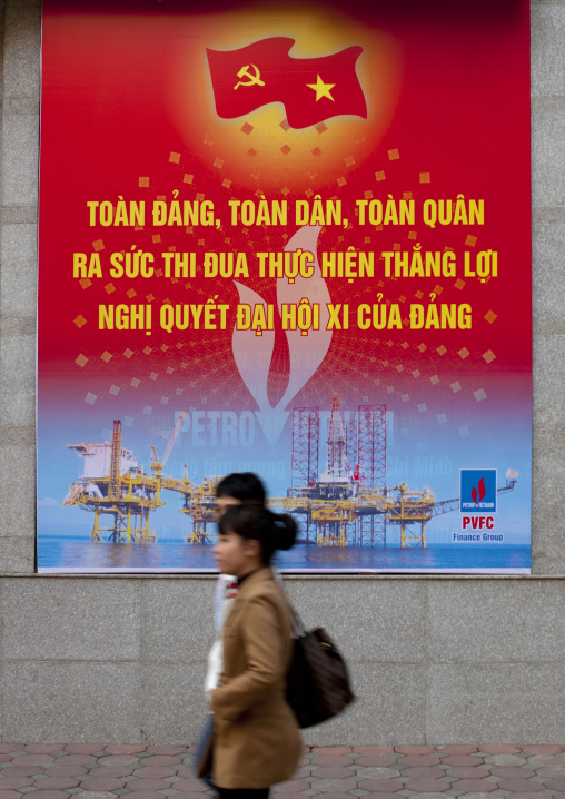 Couple passing by a propaganda billboard of the communist party, Hanoi, Vietnam