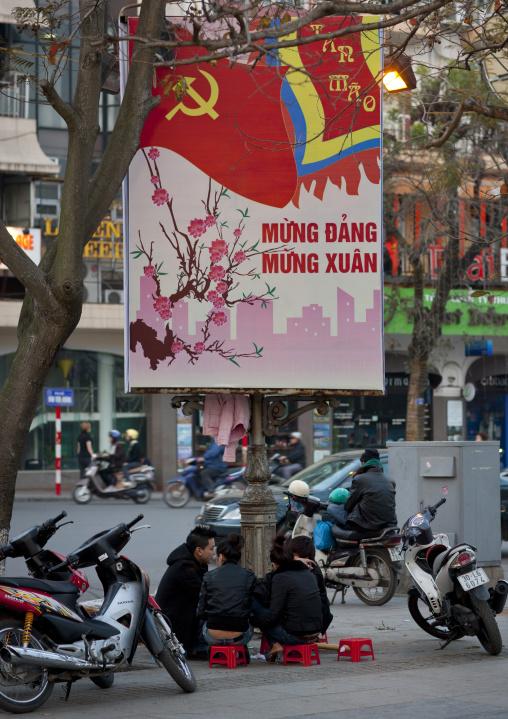 Teenagers sitting under a propaganda panel of the communist party, Hanoi, Vietnam