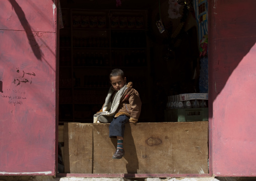 Young Boy Sitting On A Plank Barring The Entrance Of A Shop, Thula, Yemen